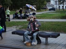 Funny musician with accordion. Mickey Mouse. Funny street musician in mask of Mickey Mouse is playing harmonica or accordion sitting on a bench. Summer evening Royalty Free Stock Image