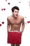 Funny naked man holding christmas gift Stock Photography
