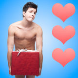 Funny naked young man with gift Royalty Free Stock Photos