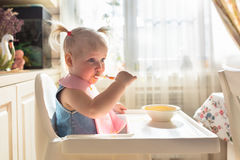 Funny naughty baby eating alone in the high chair Royalty Free Stock Photo