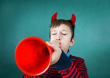 Funny naughty boy playing a toy trumpet in classroom Royalty Free Stock Photography