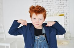 Portrait of red-haired naughty boy looking at the camera. Cute a stock photos