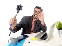 Funny nerd businessman at office desk taking selfie photo with mobile phone camera and stick Royalty Free Stock Images