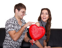 Funny nerd guy gives a valentine glamorous girl Stock Photo