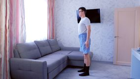 Funny nerd man is making squats exercise at home. Funny nerd man in glasses and shorts without sportswear is making squats exercise at home. Side view stock video