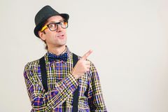 Funny nerd pointing finger away at copy space. Smiling young nerdy in glasses showing your product. Nerd man in plaid shirt and stock photography