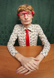 Funny nerdy guy. Funny guy sitting at the desk Royalty Free Stock Photography