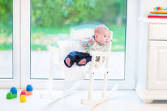 Funny newborn baby boy relaxing in rocking chair Stock Photos