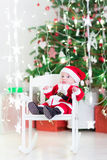 Funny newborn baby boy in Santa costume sitting under Christmas tree Stock Images