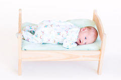 Funny newborn baby in a toy bed Stock Photo