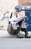 Funny News. Vintage Man Sitting In Gutter Laughs And Points In A Fit Of Hysterics When Reading The Daily Jokes Section In His Local Newspaper Royalty Free Stock Image
