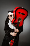 The funny nun with red guitar playing Royalty Free Stock Photos
