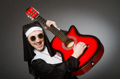The funny nun with red guitar playing Royalty Free Stock Images
