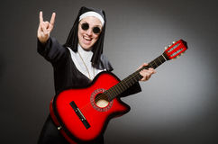 The funny nun with red guitar playing Royalty Free Stock Photography