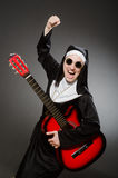 The funny nun with red guitar playing Stock Photos