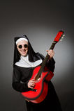 The funny nun with red guitar playing Stock Image