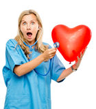 Funny nurse woman listening heart isolated on white background. Funny nurse woman listening Red heart balloon Royalty Free Stock Photography