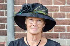 Funny old fashioned dressed dutch woman sit on brick wall background royalty free stock photos
