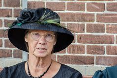 Funny old fashioned dressed dutch woman sit on brick wall background royalty free stock images