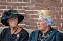 Funny old fashioned dressed dutch women sits on brick wall background royalty free stock photo
