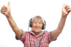 Funny old lady listening music and showing thumbs up. Royalty Free Stock Photos