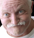 Funny old man. Making a face on a black background Royalty Free Stock Photos