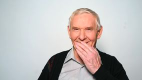Funny old man laughs covering mouth with hand.