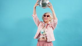 Funny old woman in sunglasses holding a ball. Lifestyle, woman wants to dance. Funny old woman in sunglasses holding a disco ball, isolated yellow background stock video footage