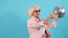 Funny old woman in sunglasses holding a disco ball. Isolated yellow background. Lifestyle, woman wants to dance stock footage