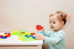 Funny one year girl having fun with modeling dough at daycare. Stock Images