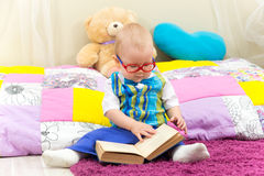 Funny one year old boy reading a book in glasses. Funny one year old boy sitting near pillows reading a book in glasses Royalty Free Stock Photos