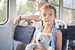 Funny open eyed girl in a tram. Small surprised girl sit in a tram with her toy teddy bear Stock Images