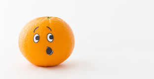 Funny orange. An orange in front of white background with a funny face showing astonishment Stock Photography