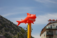 Funny orange shark with snow-white smile in the sun against the sky.  stock images