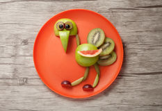 Funny ostrich made of fruits. On orange plate Royalty Free Stock Photo