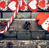 Funny outdoor Christmas composition with pine cones, lollipop, acorn, star anise, snowman and colorful felt hearts on an old. Painted wooden bench as a stock images