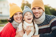 Funny overjoyed small kid laughs as has wonderful time with her parents. Affectionate parents stand near their little daughter who. Has good mood after spending royalty free stock photos