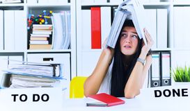 Funny overworked girl with a folder on her head sitting in the workplace cluttered with folders. Reaction of a. Subordinate when the boss orders her to do too stock image