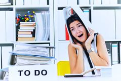 Funny overworked girl with a folder on her head sitting in the workplace cluttered with folders. Reaction of a. Subordinate when the boss orders her to do too royalty free stock photos