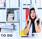 Funny overworked girl with a folder on her head sitting in the workplace cluttered with folders. Reaction of a. Subordinate when the boss orders her to do too royalty free stock photo