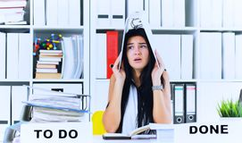 Funny overworked girl with a folder on her head sitting in the workplace cluttered with folders. Reaction of a. Subordinate when the boss orders her to do too stock photos