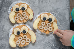 Funny owl with peanut butter and fruits on rice cake Royalty Free Stock Photos