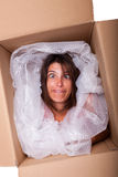 Funny package. Woman face inside a cardboard box smiling Stock Image