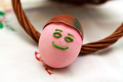 Funny painted smiling Easter egg lean on basket handle. Funny painted Easter egg in front basked with other eggs. Red ribbon Royalty Free Stock Images
