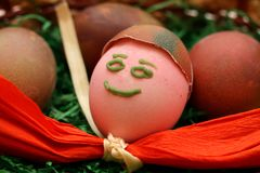 Funny painted smiling Easter egg. Funny painted Easter egg inside basked with other eggs. Red ribbon Stock Photos