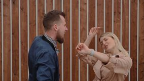 Two young male and female people are dancing outdoors near wooden wall stock video