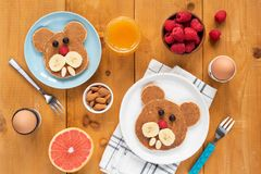 Funny pancakes foor art for kids. Healthy breakfast Table top view on a wooden table. Walrus, dog or bear shaped pancakes decorated with fruits and berries stock images