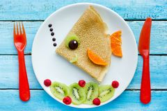 Funny pancakes with fruits shaped fish for kids breakfast. Funny pancakes with fruits shaped fish for kids stock image