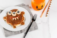 Funny pancakes for Halloween. Funny food for Halloween. Kids breakfast pancake decorated like creepy monster, with banana, berries, with pumpkin smoothie juice Royalty Free Stock Photography