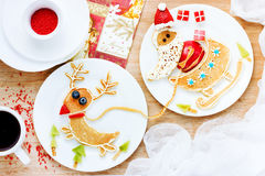 Funny pancakes Santa Claus and reindeer ride in a sleigh. Creative idea for Christmas breakfast , healthy and festive baby meal Royalty Free Stock Photo